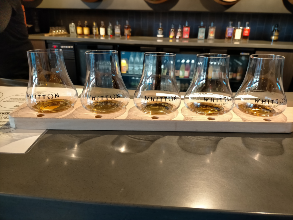Five whisky glasses are lined up on a wooden paddle. A bar is visible in the background.
