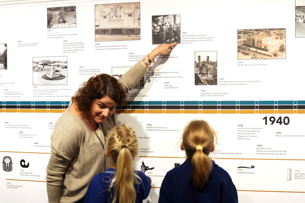 A woman is pointing to a picture on a timeline at the Leeton museum and gallery as two female children observe the wall.