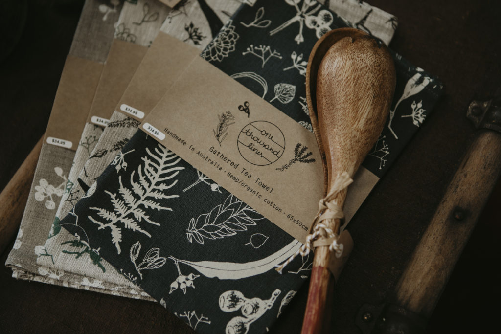 A pile of four handmade tea towels with wooden salad servers on top.