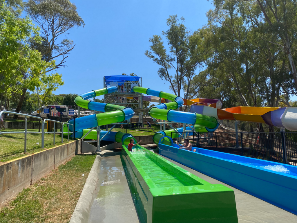 Image shows three colourful waterslides with swimmers emerging from two of them.