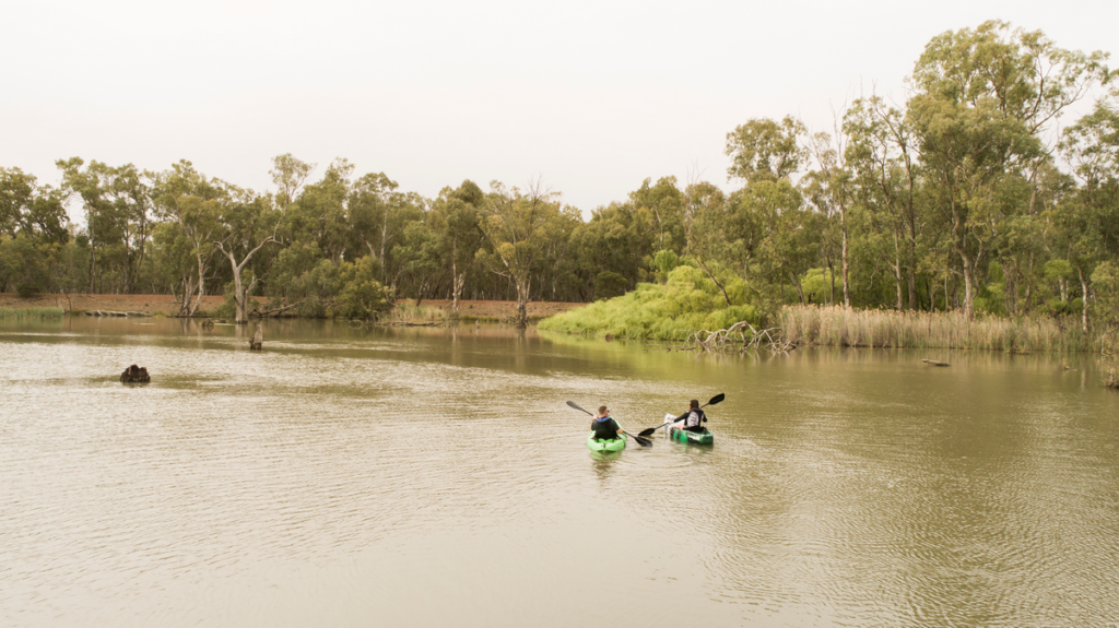 Image shows two people in canoes on the water at Rocky Waterholes, Narrandera