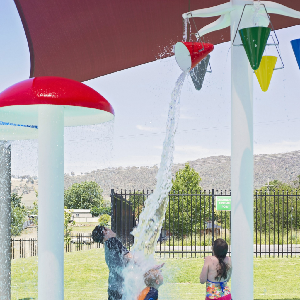 Image shows three children standing under a tower with coloured buckets suspended from it. One of the buckets is tipping water onto two of the children.