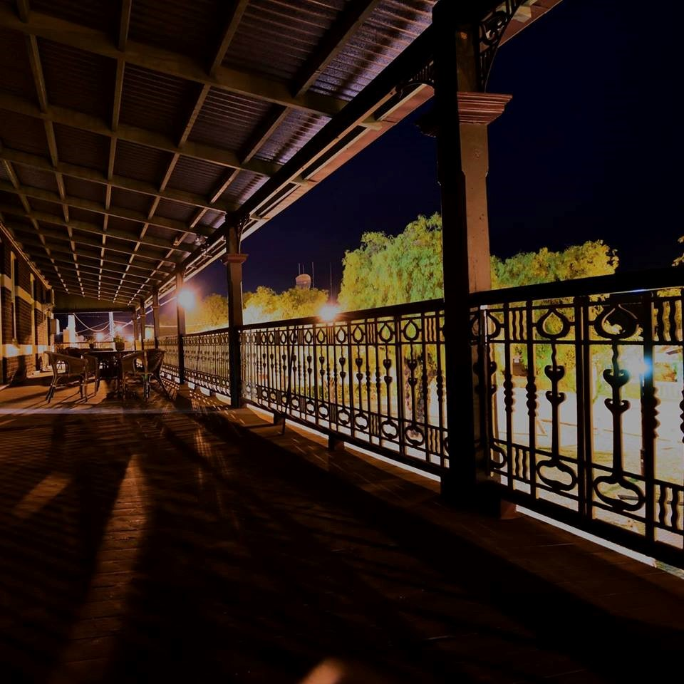 The image shows a wide verandah with decorative balustrade. It is nightime, and trees and streetlights are visible outside of the verandah.