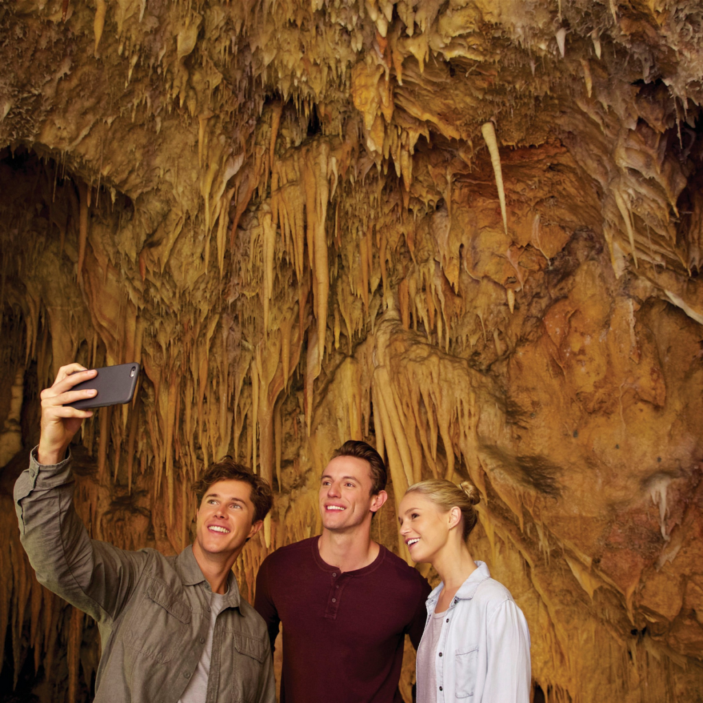 Image shows a group of two males and one female person, one male is holding a smartphone to take a selfie of the group. The group is inside a cave.