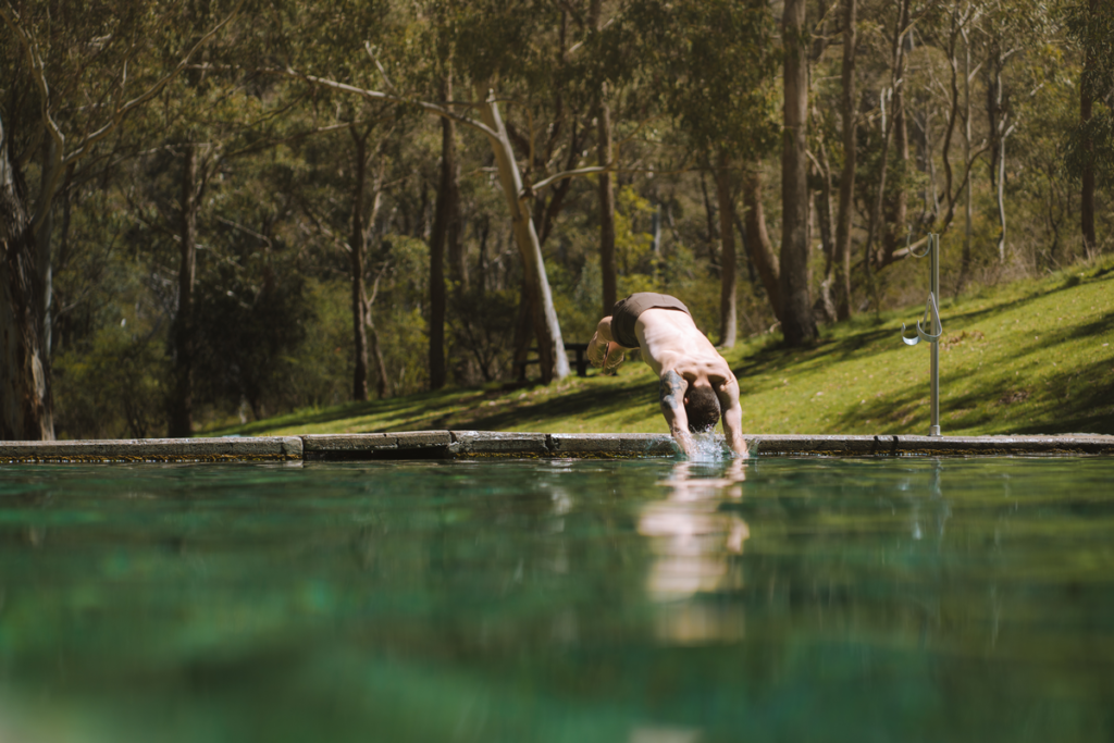 Image shows a man diving into a thermal pool, which is surrounded by forest.