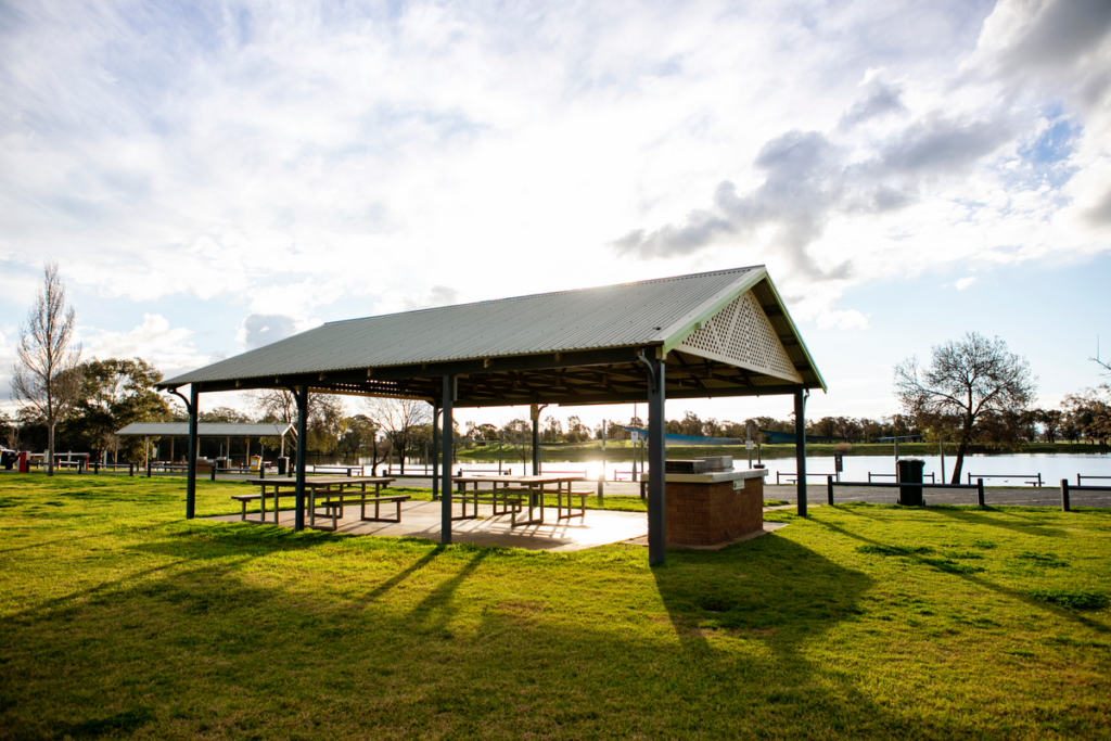 Image shows picnic tables underneath a pergola next to Lake Centenary, Temora