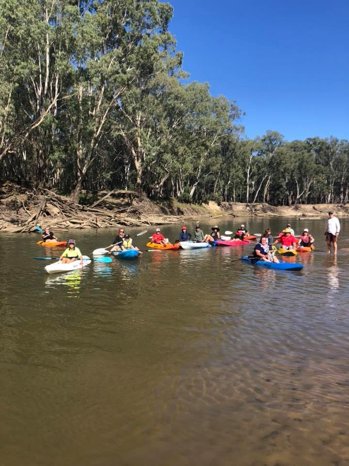 Image shows 15 people in kayaks on the murrumbidgee river and one man standing next to them.