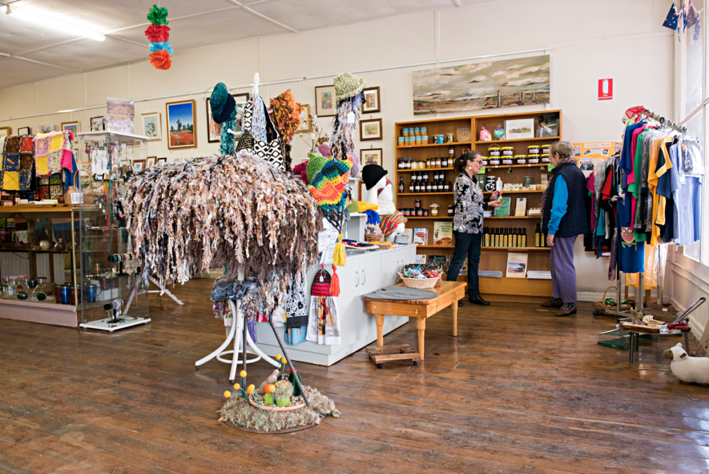 Image shows the inside of a shop and gallery filled with colourful handmade crafts, preserves and art. Two women are seen conversing next to a display.