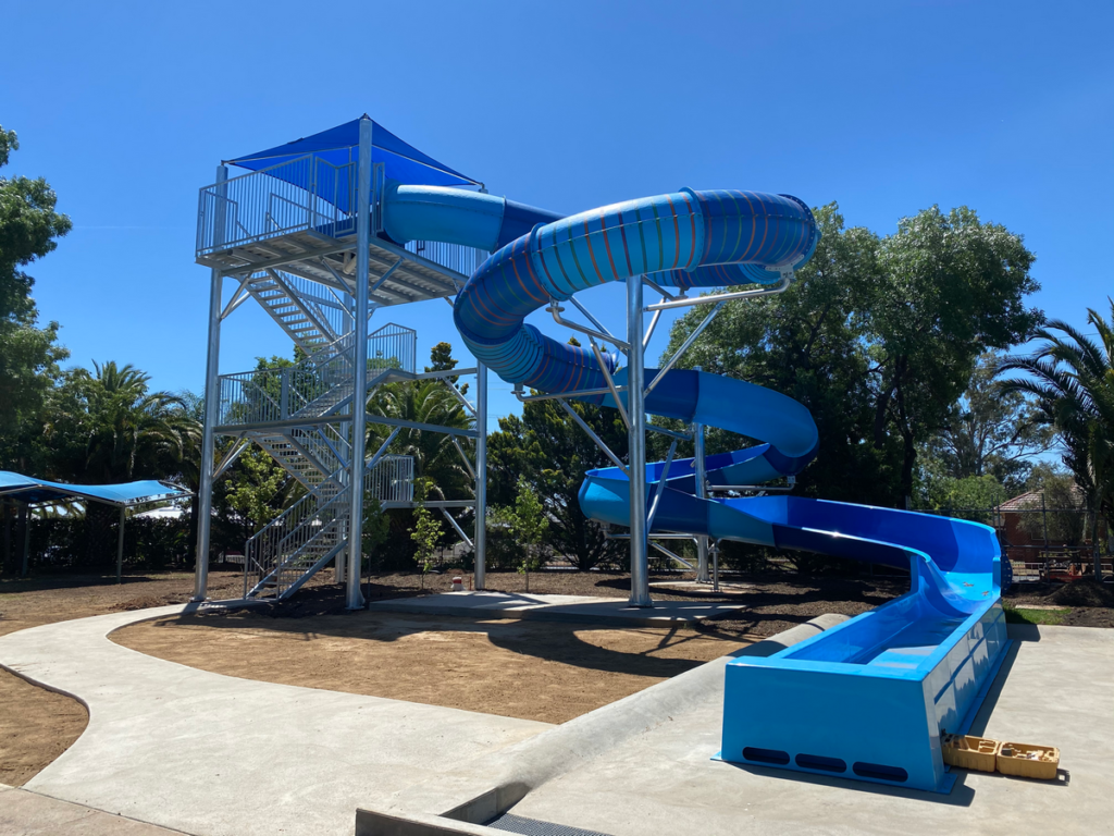 Image shows a large metal tower connected to a blue waterslide.