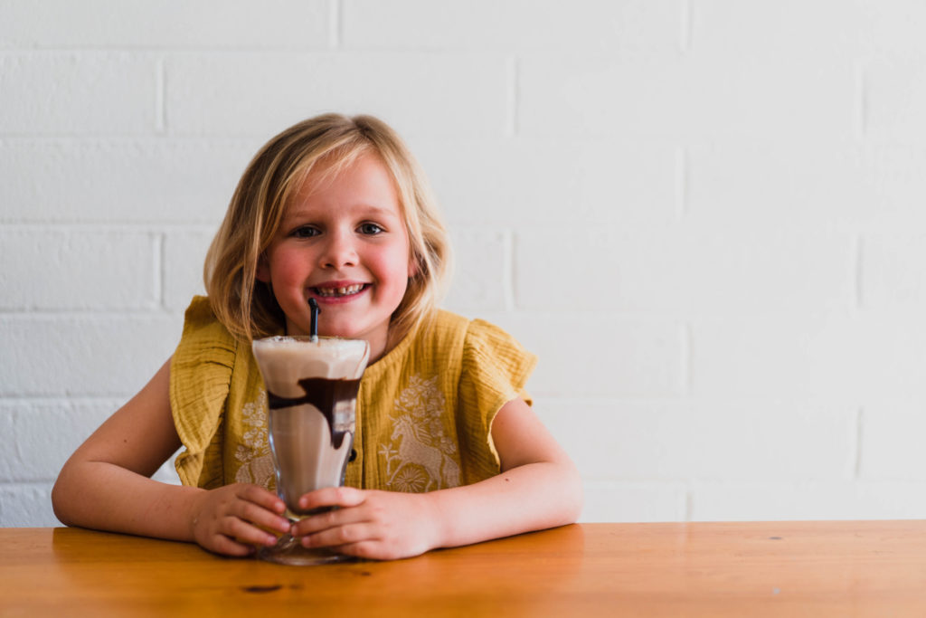 A young girl is smiling, sitting at a table and drinking a chocolate milkshake from a tall glass.