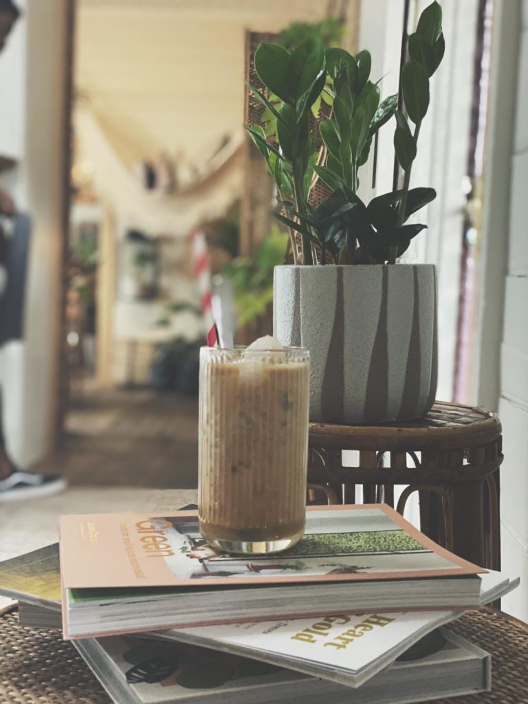 A tall glass containing a light brown drink and a red and white stripy straw sits on top of a pile of books and magazines. In the background there is a ceramic pot containing a green leafy plant, which is on top of a cane table.