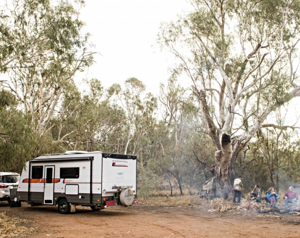 A Campervan is parked in an outback area. Four friends are gathered around a campfire.